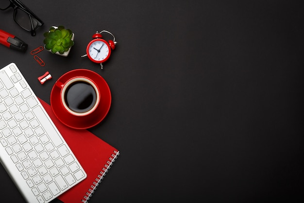 Bureau fond noir tasse café rouge note clavier réveil fleur lunettes vide