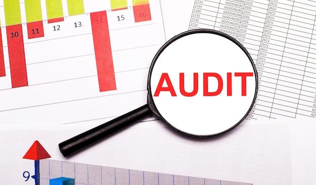 Sur le bureau, des graphiques, des rapports, une loupe avec l'inscription audit. concept d'entreprise