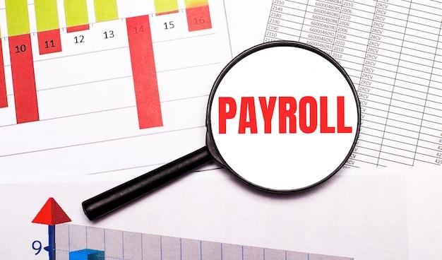 Sur le bureau, des graphiques, des rapports, une loupe avec l'inscription payroll