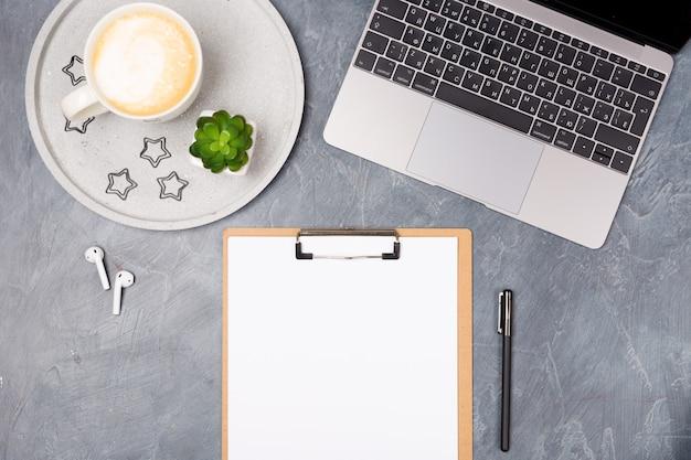 Bureau gris avec ordinateur portable argenté, écouteurs, café, liste de papier vierge et papeterie