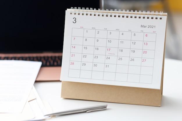 Sur le bureau, il y a un calendrier pour 2021 à côté du stylo et du papier. concept de planification des tâches quotidiennes