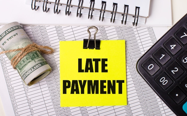 Sur le bureau, il y a des rapports, des blocs-notes, une calculatrice, une caisse et un autocollant jaune avec le texte paiement retard. concept d'entreprise