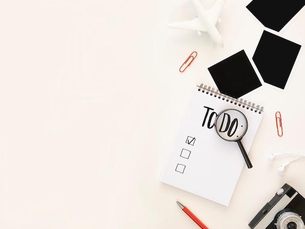 Bureau avec liste de choses à faire et objets de voyage isolés sur blanc