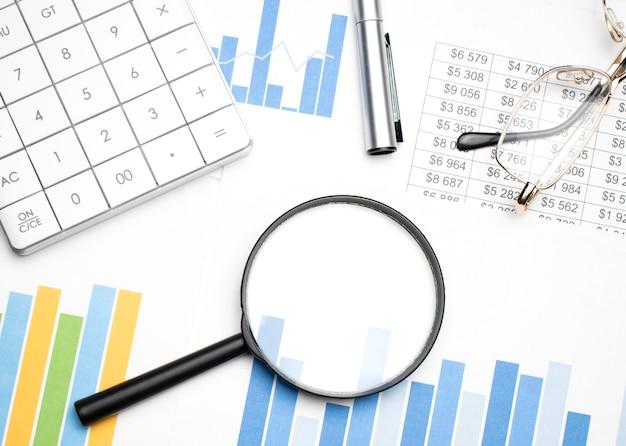 Sur le bureau, une loupe, des rapports, une calculatrice, des lunettes et un stylo. gros plan sur le lieu de travail