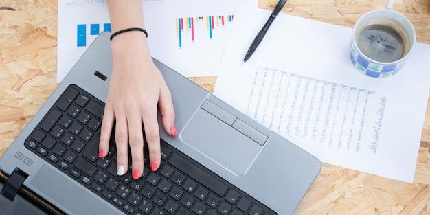 Bureau de la maison plat laïque. espace de travail féminin avec mains féminines, ordinateur portable, stylo et thé au café.