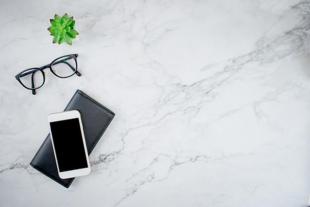 Bureau en marbre avec smartphone sur sac à main en cuir noir, lunettes et plante