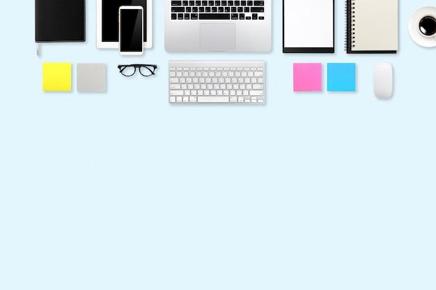 Bureau de marketing numérique avec ordinateur portable, fournitures de bureau, tasse à café et téléphone portable sur pastel vert