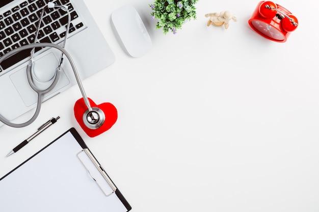 Bureau médical avec stéthoscope, coeur, stylo, ordinateur portable, souris et film radiographique sur un bureau blanc.