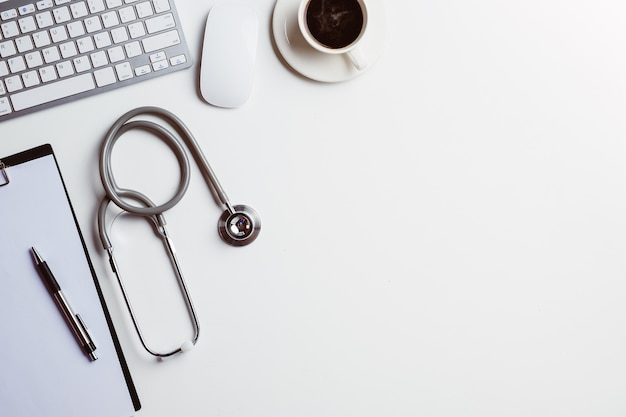 Bureau médical avec stéthoscope, coeur, stylo, ordinateur portable, souris et tasse de café sur un bureau blanc.top v