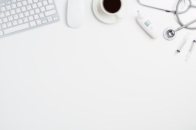 Bureau médical avec stéthoscope, thermomètre numérique, stylo, ordinateur portable, souris et tasse de café sur wh