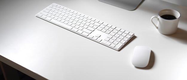 Bureau minimal avec appareils informatiques, tasse à café et espace de copie