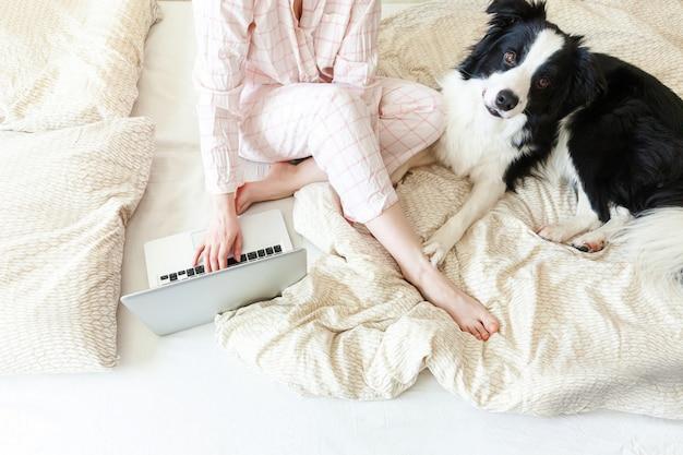 Bureau mobile à domicile. jeune femme en pyjama assis sur le lit avec chien de compagnie travaillant à l'aide d'un ordinateur portable pc à la maison. fille de style de vie étudie à l'intérieur. concept de quarantaine d'entreprise indépendant.
