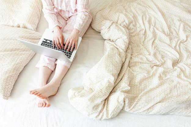 Bureau mobile à domicile. jeune femme en pyjama assis sur le lit à la maison travaillant à l'aide d'un ordinateur portable pc. fille de style de vie étudie à l'intérieur. concept de quarantaine d'entreprise indépendant.