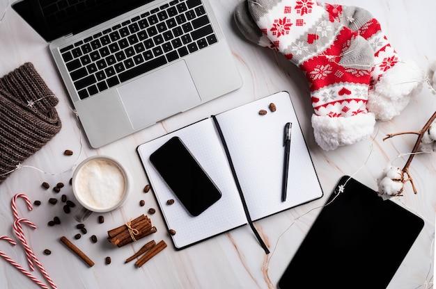 Bureau de noël avec ordinateur portable, tablette et téléphone intelligent entouré de bas, de cannes de bonbon et de café