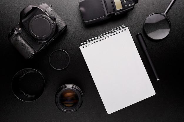 Bureau noir avec ordinateur portable, appareil photo, crayon et loupe
