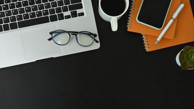 Bureau noir avec ordinateur portable, téléphone intelligent, tasse à café, lunettes et ordinateur portable.