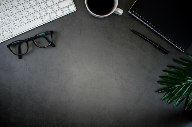 Bureau avec ordinateur portable, café, clavier et accessoires