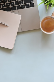 Bureau d'ordinateur portable comprenant une tasse à café, un crayon, un ordinateur portable et une plante en pot sur une table en marbre.