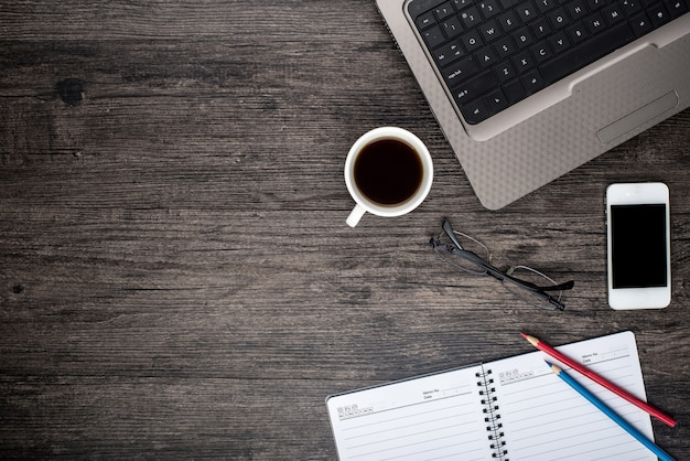 Bureau avec un ordinateur portable, une tasse de café et un calendrier