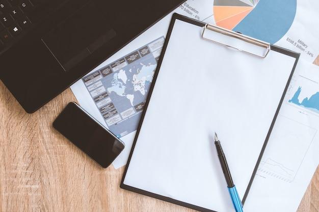 Bureau ordonné de l'homme d'affaires et des outils de travail avec la paperasse, ordinateur, appareils à écran tactile et papeterie sur une surface en bois, vue de dessus