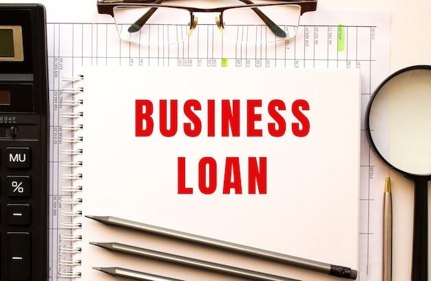 Bureau avec papiers financiers, loupe, calculatrice, lunettes. page du bloc-notes avec le texte business loan. vue d'en-haut. concept d'entreprise.