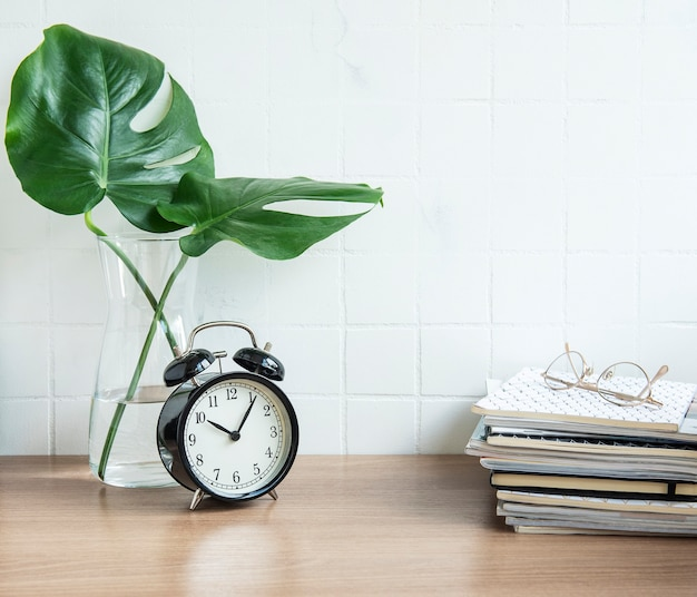 Bureau avec pile de blocs-notes, réveil, fournitures de bureau et plantes d'intérieur