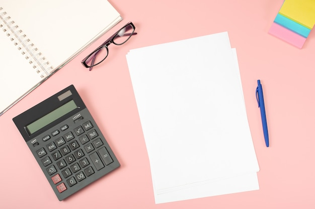Bureau à plat. une feuille de papier blanc vierge avec un stylo est au-dessus de la table de bureau rose avec calculatrice et suppléments.