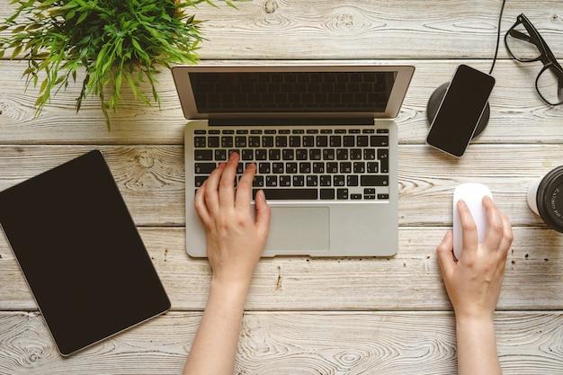 Bureau plat laide espace de travail avec une main féminine, vue de dessus d'ordinateur portable