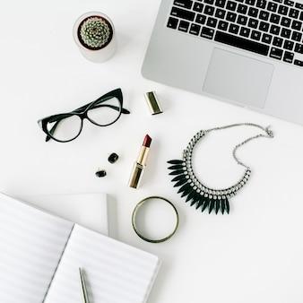 Bureau plat, vue de dessus. espace de travail avec ordinateur portable, accessoires féminins, lunettes, cactus, agenda, rouge à lèvres, collier sur blanc.