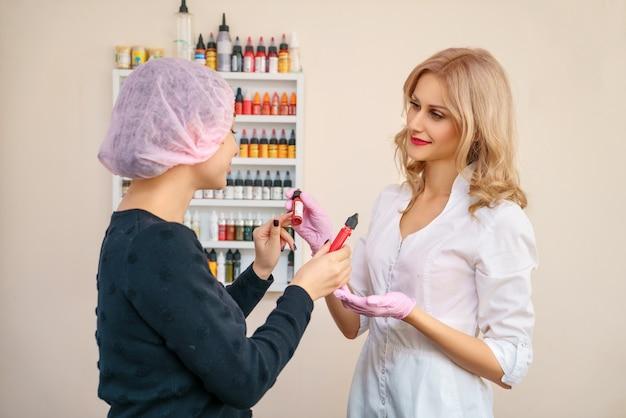Bureau pour le tatouage des sourcils et des lèvres, le client choisit la couleur pour le tatouage.