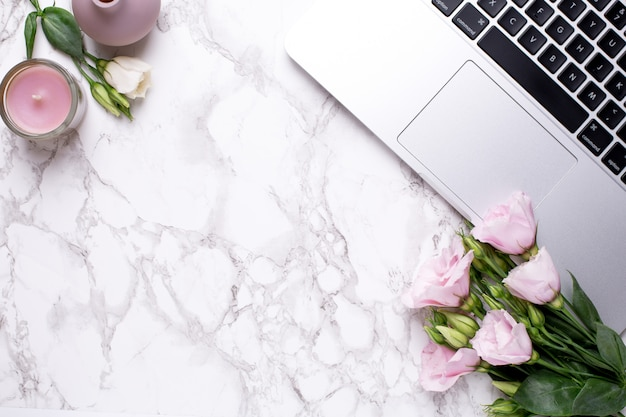 Bureau romantique avec des fleurs, des bougies et un clavier sur une table de marbre