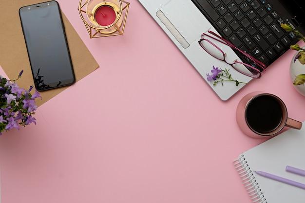 Bureau rose plat moderne espace de travail avec ordinateur portable, lunettes, smartphone, tasse à café.