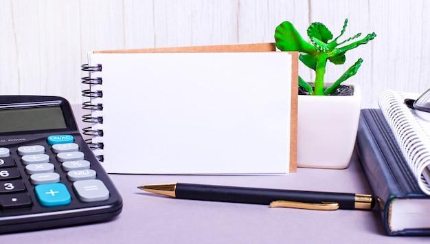 Sur le bureau se trouvent une calculatrice, des agendas, une plante en pot, un stylo et un cahier vierge avec un emplacement pour insérer du texte. concept d'entreprise. gros plan sur le lieu de travail