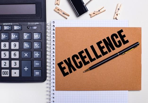 Sur le bureau se trouvent une calculatrice, un stylo et des pinces à linge près d'un cahier avec le texte excellence. concept d'entreprise. vue d'en-haut