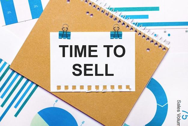 Sur le bureau se trouvent des graphiques et des diagrammes bleus et bleu clair, un cahier marron et une feuille de papier avec des clips bleus et du texte time to sell. vue d'en-haut. concept d'entreprise
