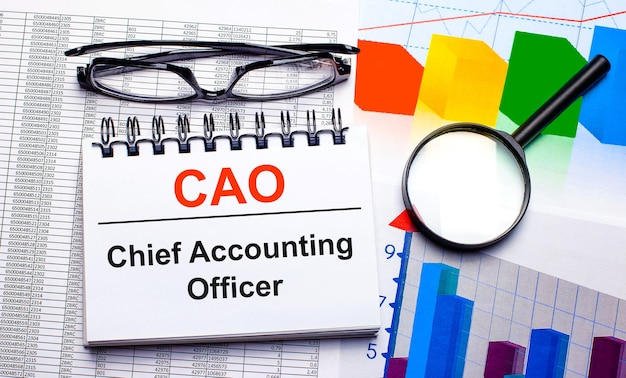 Sur le bureau se trouvent des lunettes, une loupe, des nuanciers et un cahier blanc avec le texte cao chief accounting officer. concept d'entreprise. vue d'en-haut
