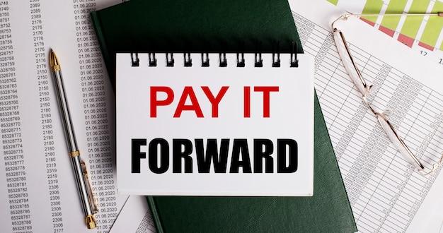 Sur le bureau se trouvent des rapports, des lunettes, un stylo, un journal vert et un cahier blanc avec les mots pay it forward. gros plan sur le lieu de travail