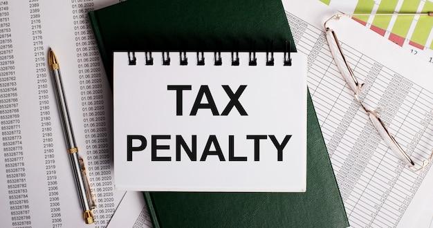 Sur le bureau se trouvent des rapports, des lunettes, un stylo, un journal vert et un cahier blanc avec les mots penalite fiscale. gros plan sur le lieu de travail. concept d'entreprise
