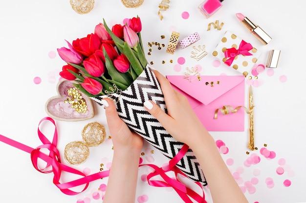 Bureau de style rose et or avec des fleurs. tulipes roses en papier d'emballage élégant noir et blanc, cadeaux, cosmétiques et accessoires féminins avec des confettis sur fond blanc