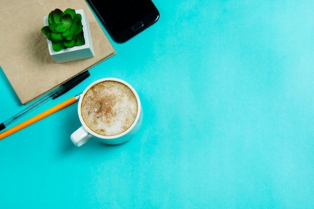Bureau table bureau. espace de travail avec smartphone, fournitures de bureau, sur fond bleu.