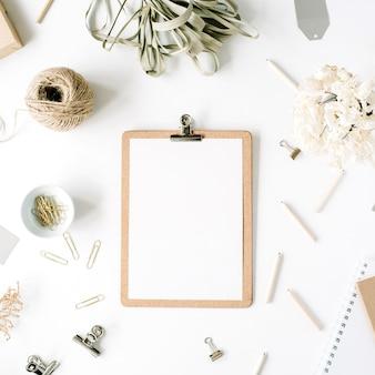 Bureau de table de bureau plat lapointe, vue de dessus. espace de travail de bureau féminin avec presse-papiers, ficelle, crayons, bouquet floral, journal d'artisanat et clips sur fond blanc.
