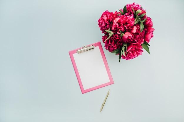 Bureau de table de bureau plat minimaliste avec presse-papiers, bouquet de fleurs de pivoine rose sur surface bleue
