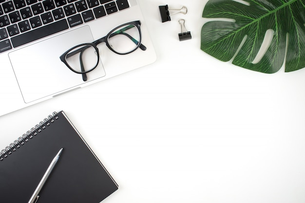 Bureau de table de bureau plat poser, vue de dessus. workspace a un ordinateur portable, un cahier, un stylo, un presse-papiers, des lunettes et des feuilles avec une zone de copie.
