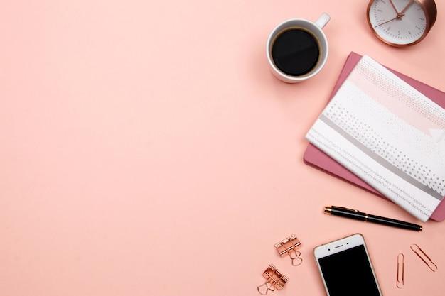 Bureau table bureau avec smartphone et autres fournitures de bureau sur fond rose.