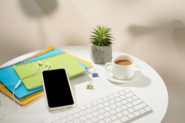 Bureau de table de bureau vue de dessus. espace de travail avec téléphone portable et fournitures de bureau sur fond blanc.