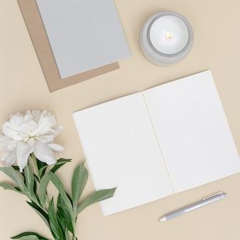 Bureau de table de bureau vue de dessus à plat espace de travail avec stylo de cahier vierge fleur de pivoine blanche
