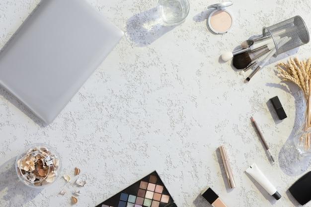 Bureau de table confortable avec ordinateur portable et accessoires de maquillage beauté, vue de dessus et plat poser. espace de travail de bureau de mode maison femmes sur fond de plâtre avec lumière dure moderne et ombres.