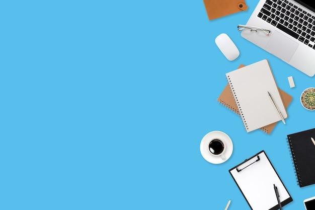 Bureau de table d'espace de travail à plat avec ordinateur portable, fournitures de bureau, tasse à café, tablette et smartphone mobile sur fond de couleur
