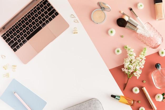 Bureau table pastel avec ordinateur portable, feuilles, fleurs printanières, presse-papiers et accessoires de beauté, vue de dessus.