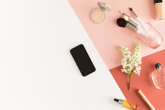 Bureau table pastel avec téléphone portable, fleurs de printemps, presse-papiers et accessoires de beauté, vue de dessus,
